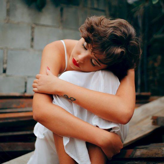 Depressed Woman Hugging Herself and Practicing Self-Love