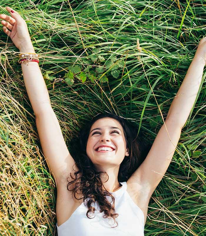 Happy woman lying in grass